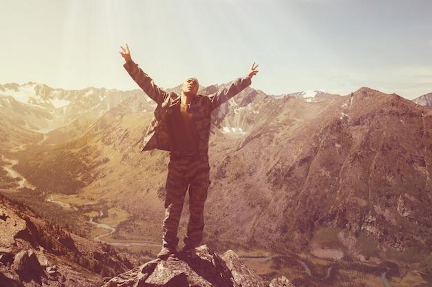Alpinista de pé no topo de uma montanha com as mãos levantadas e apreciando o nascer do sol. turistas de braços erguidos ao fundo de uma bela paisagem montanhosa com um lago e um rio
