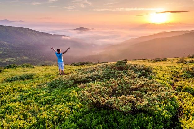 Alpinista de pé no topo de uma montanha com as mãos levantadas e apreciando o nascer do sol
