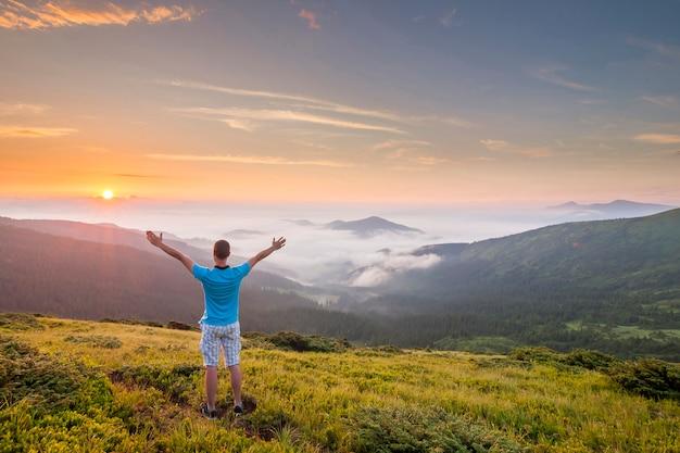Alpinista de pé no topo de uma montanha com as mãos levantadas