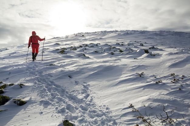 Alpinista de turista em roupas vermelhas brilhantes com bengalas descendo a encosta da montanha rochosa perigosa coberta de neve no fundo do espaço da cópia do céu nublado tempestuoso.