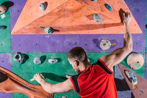 Alpinista de vista traseira na parede