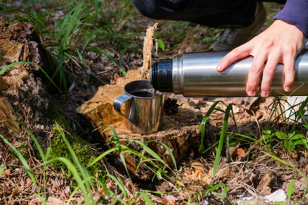 Alpinista derrama chá de uma garrafa térmica em uma floresta de verão