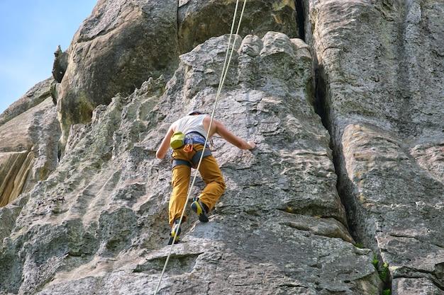Alpinista determinado escalando parede íngreme de uma montanha rochosa. esportista superando rota difícil. envolvendo-se em esportes radicais e conceito de passatempo de escalada em rocha.