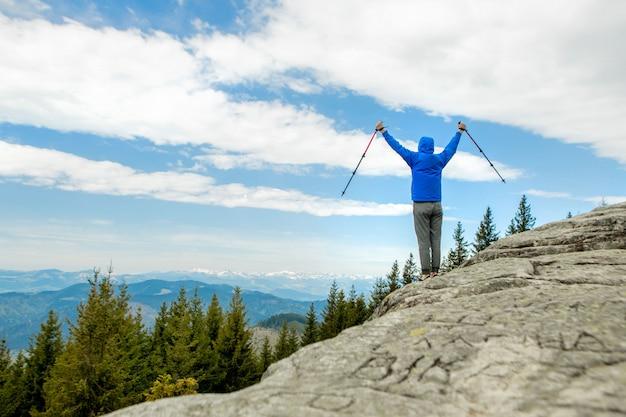 Alpinista é alto nas montanhas contra o céu, comemorando a vitória, levantando as mãos.