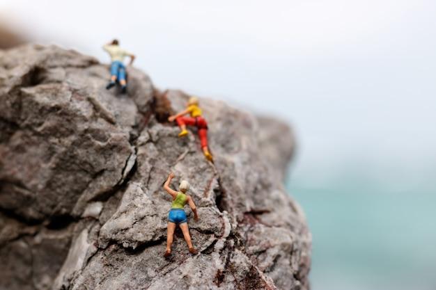 Alpinista em miniatura em uma rocha