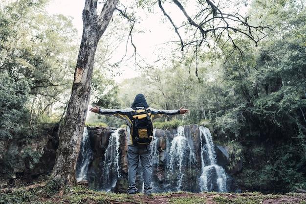Alpinista em pé com os braços estendidos em frente a uma cachoeira.