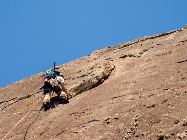 Alpinista escalando uma parede de rocha inclinada no brasil