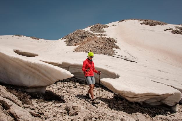 Alpinista feminina com bengalas entre pedaços de neve