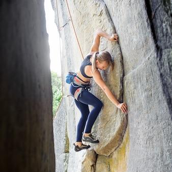 Alpinista feminina escalada com corda em uma parede rochosa