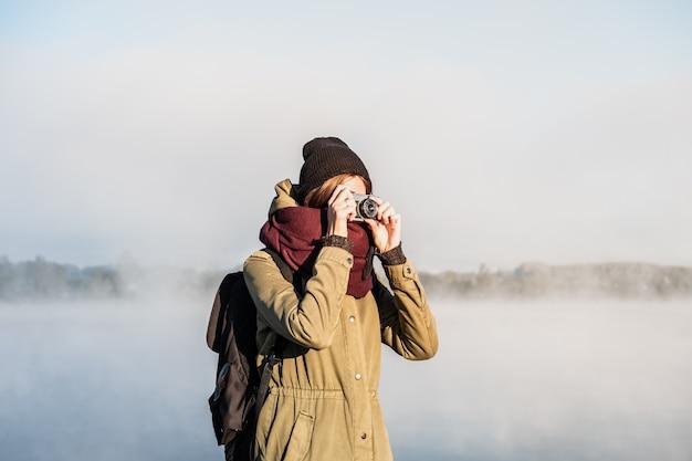 Alpinista feminina fotografando belas paisagens naturais cobertas de névoa. mulher usa uma câmera de filme vintage parada no lindo parque natural ao amanhecer