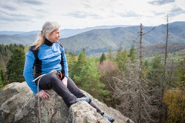 Alpinista feminina no pico da rocha com equipamento de escalada