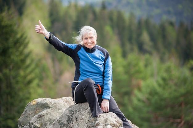 Alpinista feminina no pico da rocha