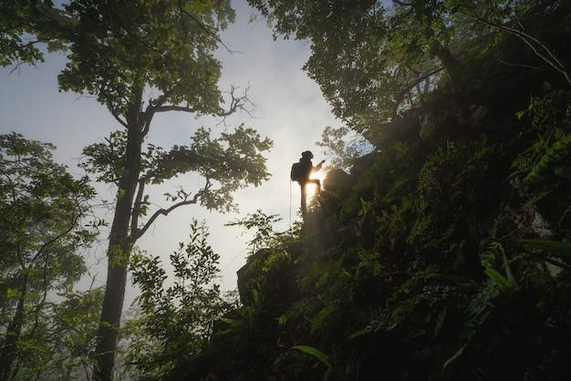Alpinista feminina no topo das colinas com os braços abertos durante o nascer do sol