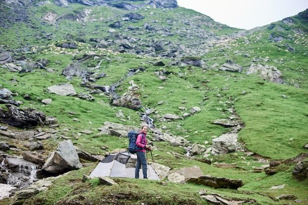 Alpinista feminina, olhando para a câmera, de pé na rocha perto da tenda na encosta rochosa verde nas montanhas