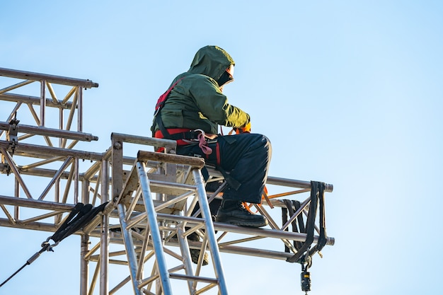 Alpinista industrial em uniforme sentado st em uma estrutura de construção