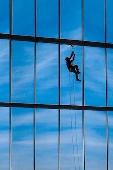 Alpinista industrial paira de cordas no interior do edifício