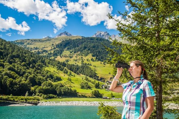Alpinista jovem nas montanhas com um telescópio