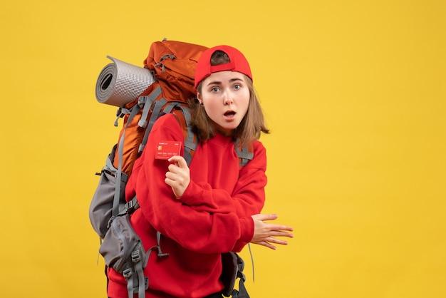 Alpinista linda de frente para mulher com mochila segurando cartão de desconto