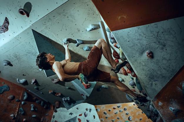Alpinista livre escalando pedra artificial dentro de casa