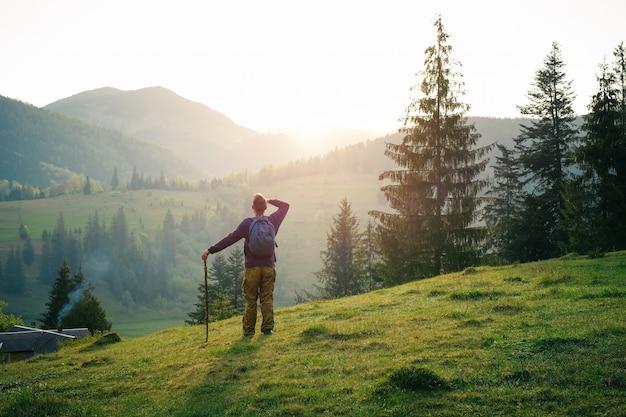 Alpinista masculina caucasiana com uma vara de madeira nas montanhas