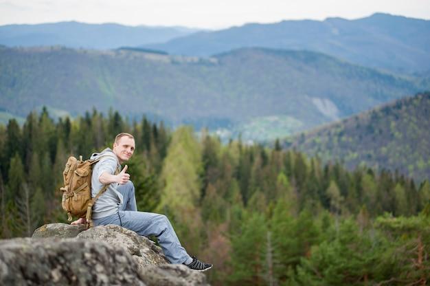 Alpinista masculina com mochila marrom no pico da rocha