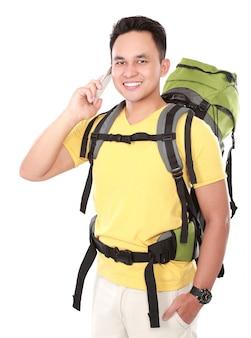 Alpinista masculina com mochila usando telefone celular