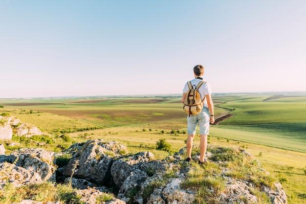 Alpinista masculina em pé em cima de rocha, olhando a paisagem verde