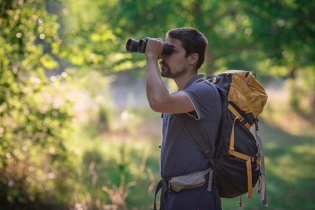 Alpinista masculina, olhando através de binóculos na floresta