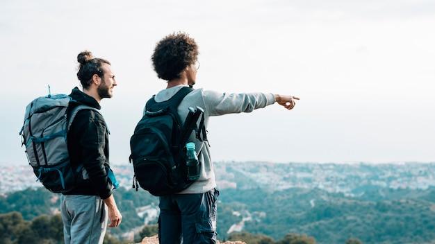 Alpinista masculina, olhando para o dedo apontando jovem africano sobre a paisagem urbana