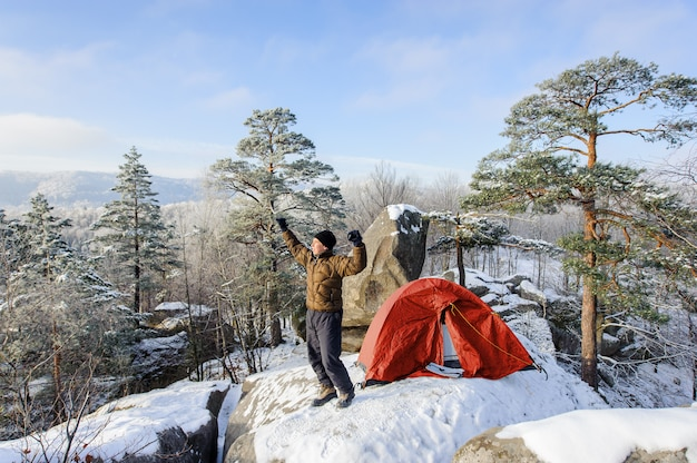 Alpinista masculina quase sua tenda no topo da rocha