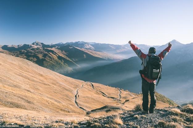 Alpinista masculina relaxante ao pôr do sol no cume da montanha e olhando majestoso panorama