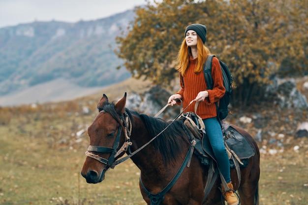 Alpinista mulher monta um cavalo na natureza nas montanhas. foto de alta qualidade