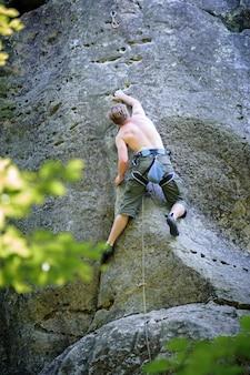 Alpinista muscular sobe na parede do penhasco com corda
