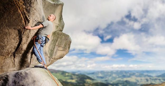Alpinista no precipício de rocha saliente íngreme