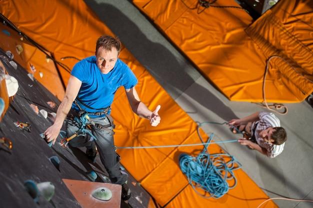 Alpinista praticando escalada na parede de rocha dentro de casa