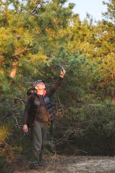 Alpinista procurando seu sinal de gps em um smartphone, desorientado em uma floresta exuberante, tentando encontrar uma saída