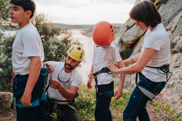 Alpinista profissional e sua esposa na casa dos 30 anos preparando seus alunos para escalar uma montanha com segurança