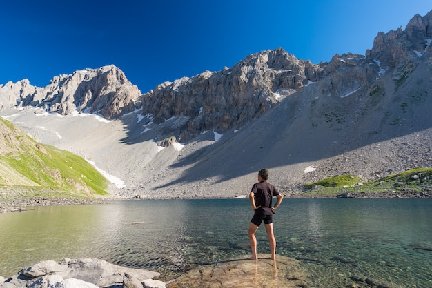 Alpinista relaxante no lago azul de alta altitude em ambiente não contaminado idílico