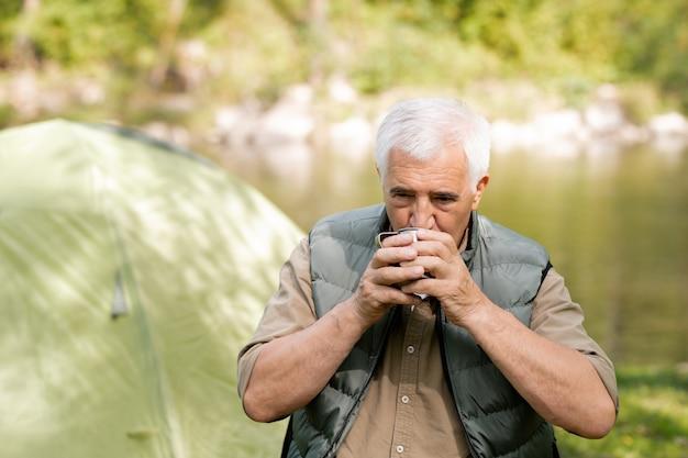 Alpinista sênior com cabelos grisalhos bebendo chá quente de uma caneca de turista enquanto descansa após um longo caminho em ambiente natural