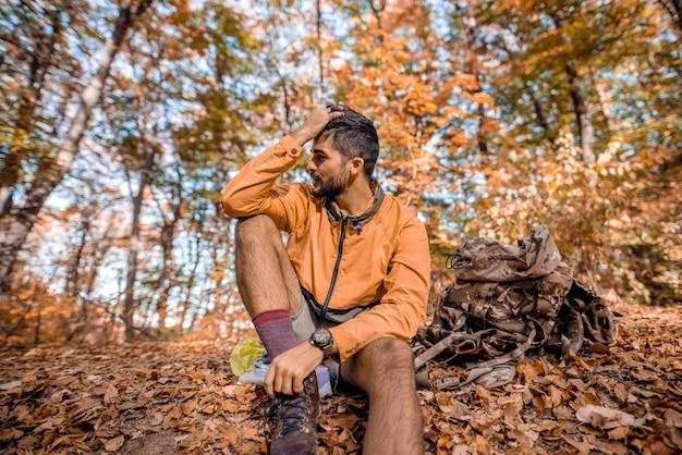 Alpinista sentado no chão na floresta no outono.