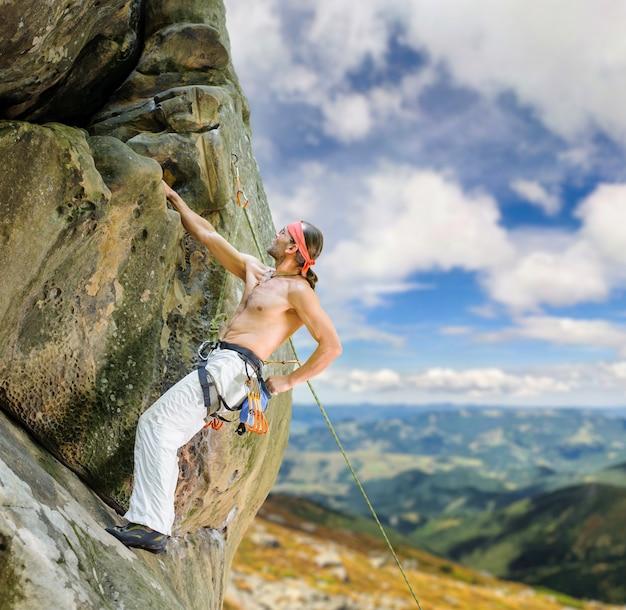 Alpinista sobe com corda no penhasco saliente
