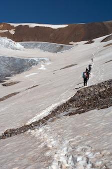 Alpinista subindo pelo campo de neve até o alto cume