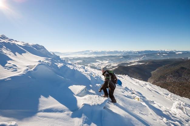 Alpinista turista alpinista em roupas de inverno com mochila escalando encosta de montanha rochosa íngreme perigosa coberto com neve profunda, raios de sol branco brilhando no fundo de espaço de cópia de céu azul brilhante.