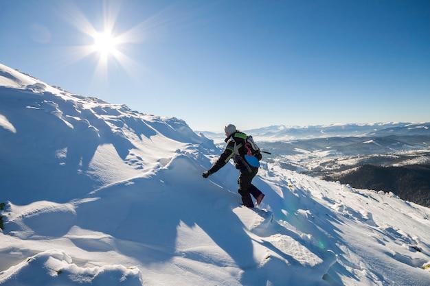 Alpinista turista alpinista em roupas de inverno com mochila escalando encosta de montanha rochosa íngreme perigosa coberto com neve profunda, raios de sol branco brilhando no fundo do espaço da cópia do céu azul brilhante.