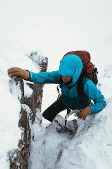 Alpinista usando um machado de gelo para escalar forcan ridge em glen shiel, escócia