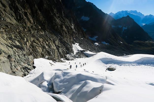 Alpinistas amarrados escalando montanha com campo de neve amarrado com uma corda com machados de gelo e capacetes