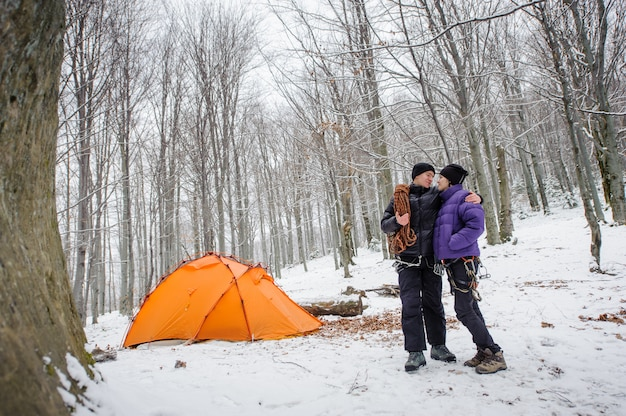 Alpinistas de pé ao lado do acampamento base de montanhas de inverno