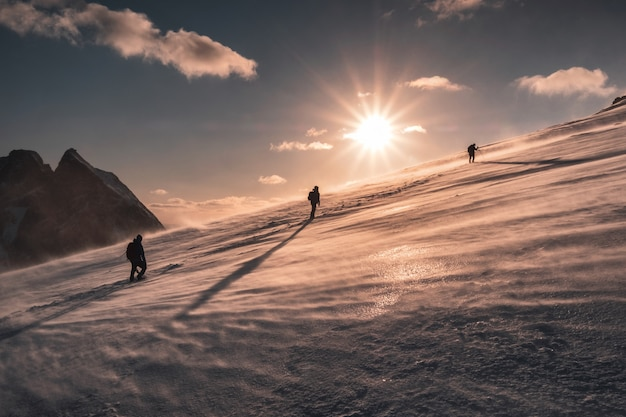 Alpinistas escalada na nevasca na colina de neve ao pôr do sol