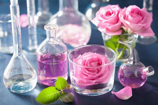 Alquimia e aromaterapia com flores rosas e frascos químicos