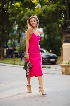 Alta altura cheia de estatura elegante sorridente feliz mulher atraente com vestido rosa sexy de verão andando na rua segurando bolsa